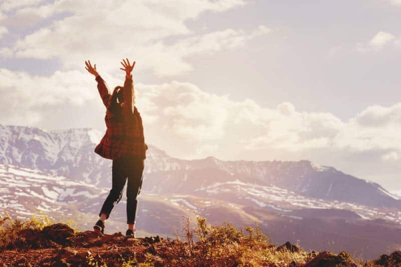 happy woman raising her hands on mountain