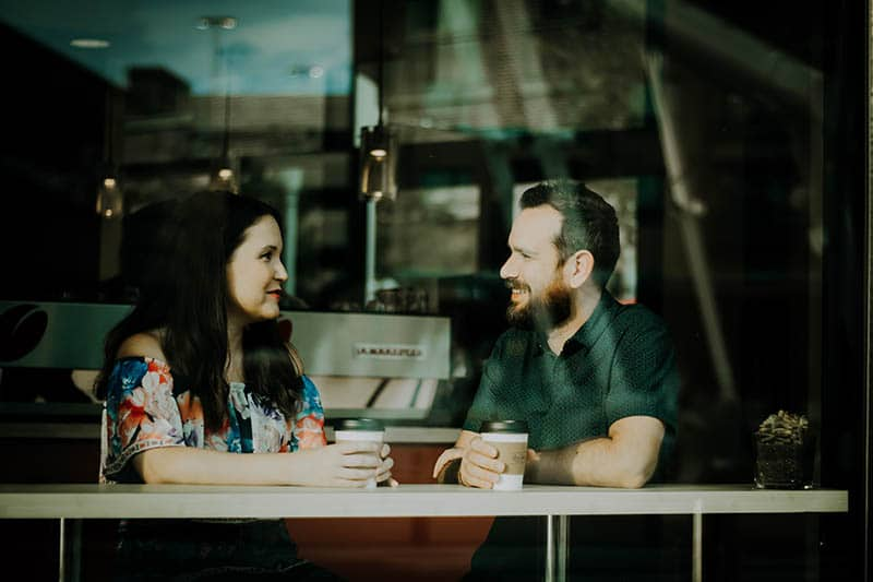 man and woman sitting at cafe and looking each other