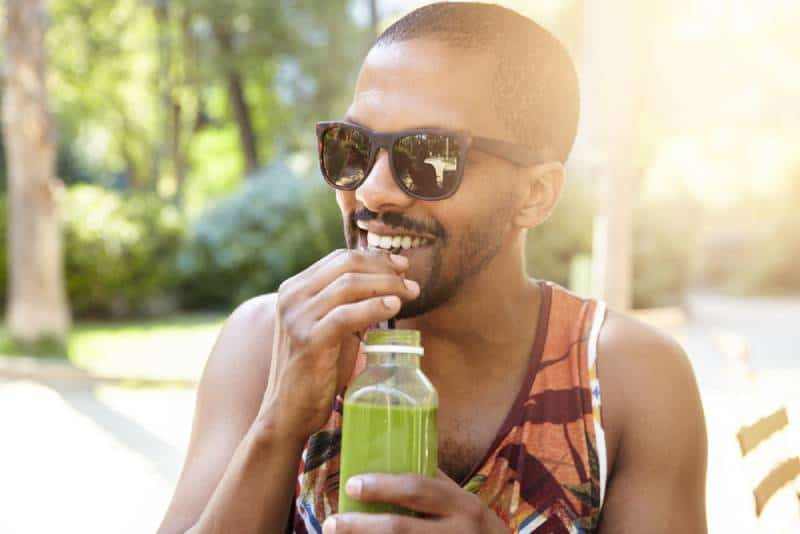 man drinking cocktail from plastic bottle