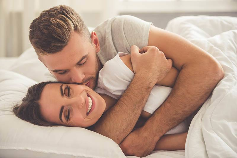 man hugging smiling woman from back on bed