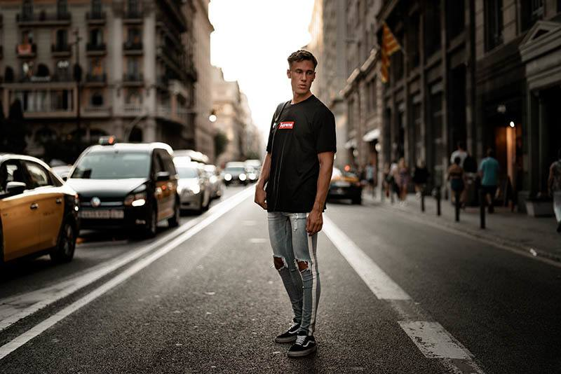man in blue jeans and black tshirt standing on road near cars