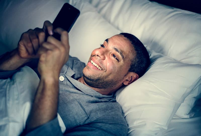 man in pajamas lying on bed and typing on his phone