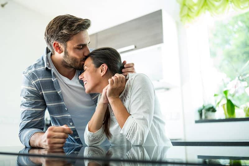 man kissing woman in head