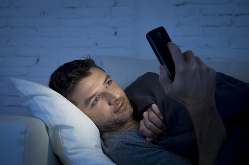 man lying on couch and typing on his phone