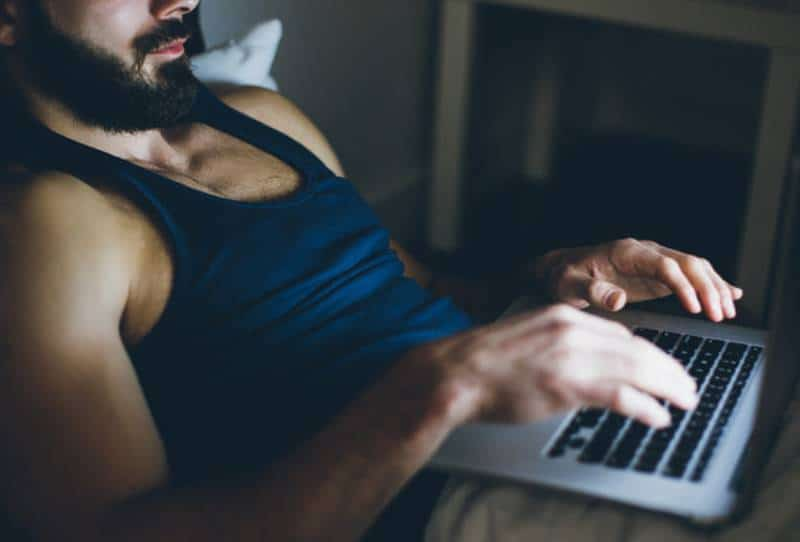 man typing on his laptop before sleep