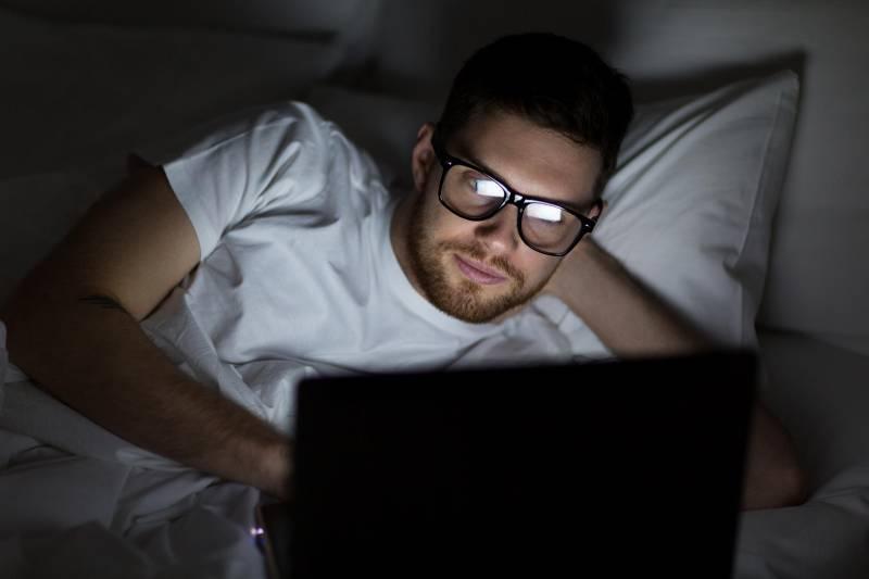 man wearing eyeglasses typing on his laptop before sleep