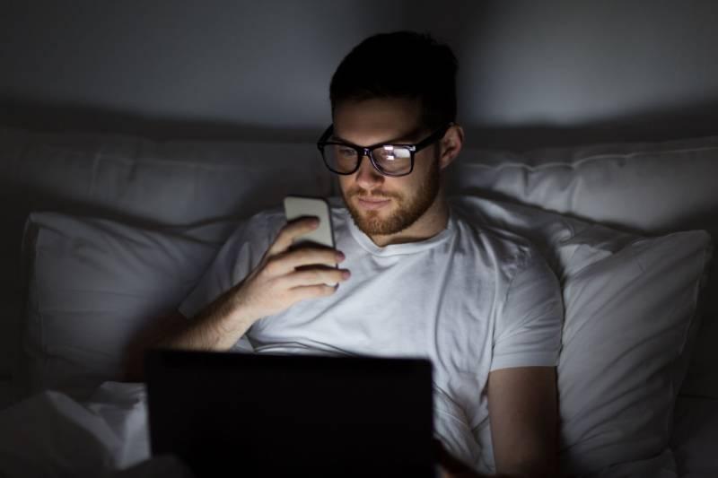 man wearing eyeglasses typing on his phone before sleep