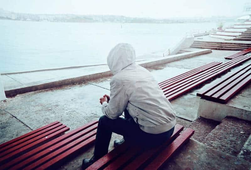 man wearing hoodie sitting beside water