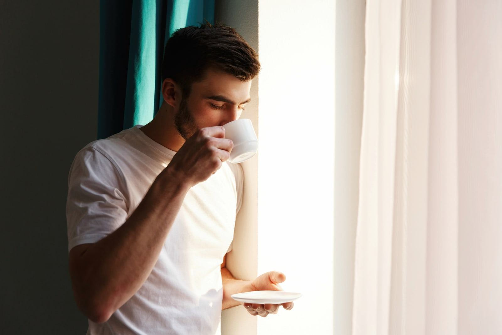 man wearing white t shirt drinking coffee