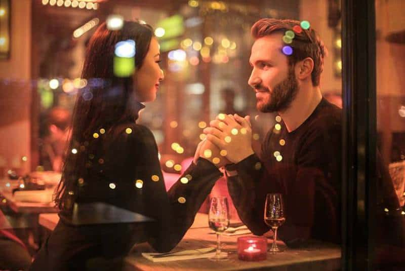 romantic couple looking each other while having a dinner in restaurant