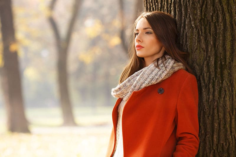 sad woman in red coat standing in nature