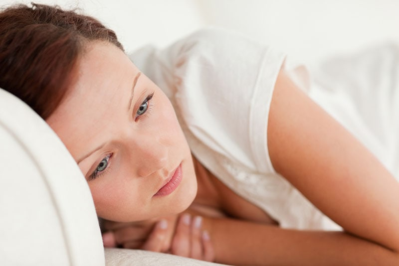 sad woman lying in bed and thinking