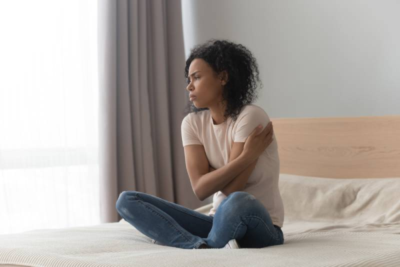 sad woman sitting in bed at home alone