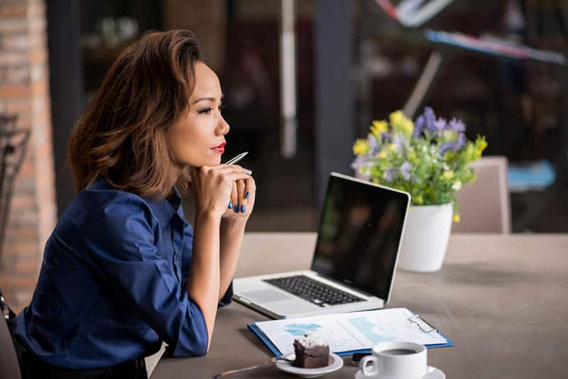 side view of beautiful woman sitting on table with laptop