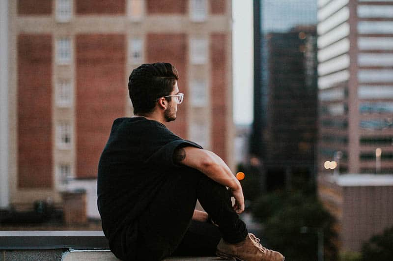 side view of man wearing eyeglasses and black tshirt sitting on rooftop