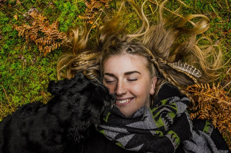 smiling woman lying on the ground next to black dog during the day