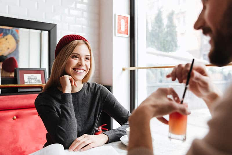 smiling woman with red hat looking at man in cafe