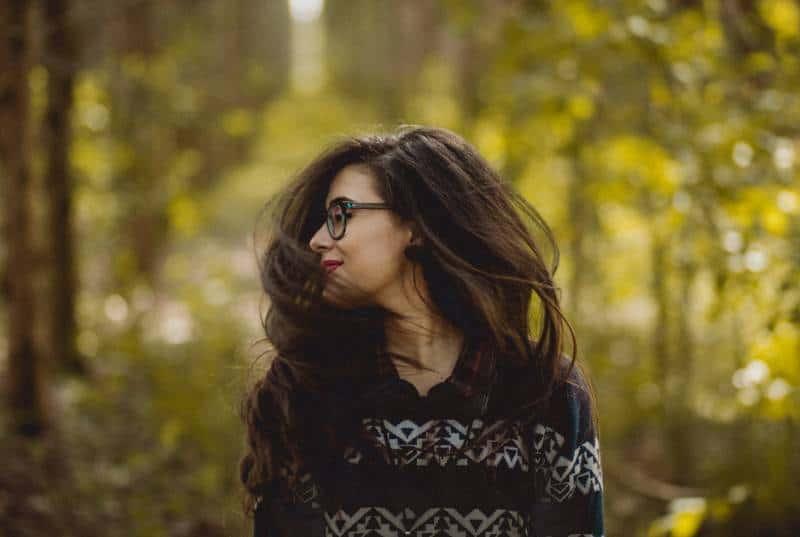 woman posing beside trees