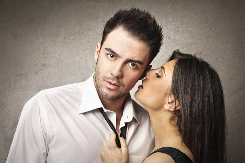 woman whispering to man's ear