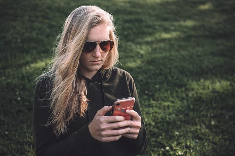 woman with glasses reading a text message