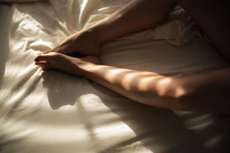 woman's feet on white bedspread