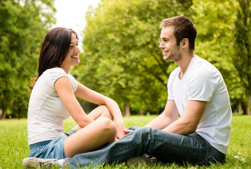 young couple sitting on grass in nature