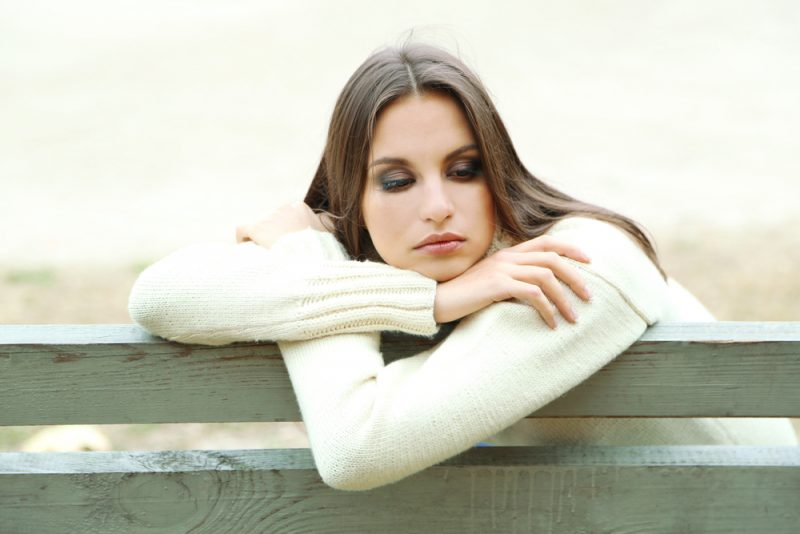 young lonely woman sitting on the bench