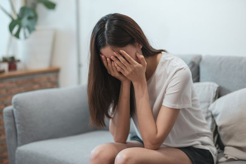 young woman crying on the couch