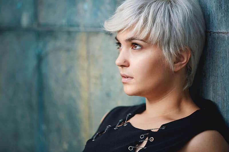 young woman with short blond hair looking away