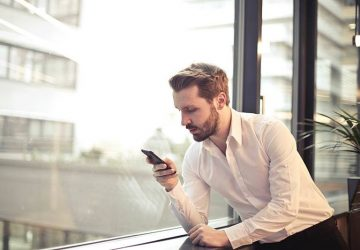 man in white shirt typing on his phone beside window