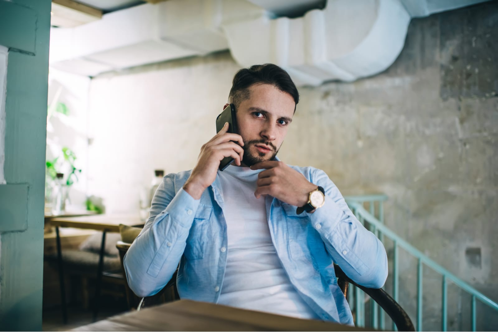 a serious man in a blue shirt is sitting in a cafe and calling someone on his cell phone