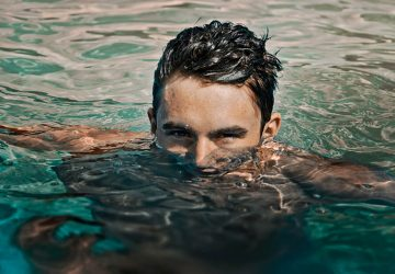 man in water with half face over water