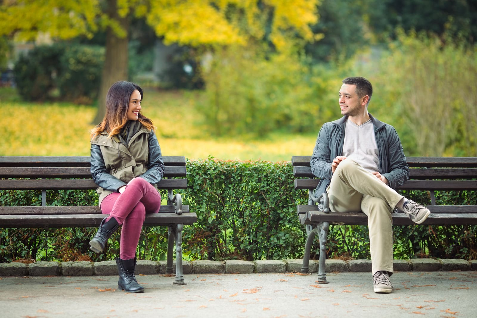 smiling man and woman sitting on the park bench