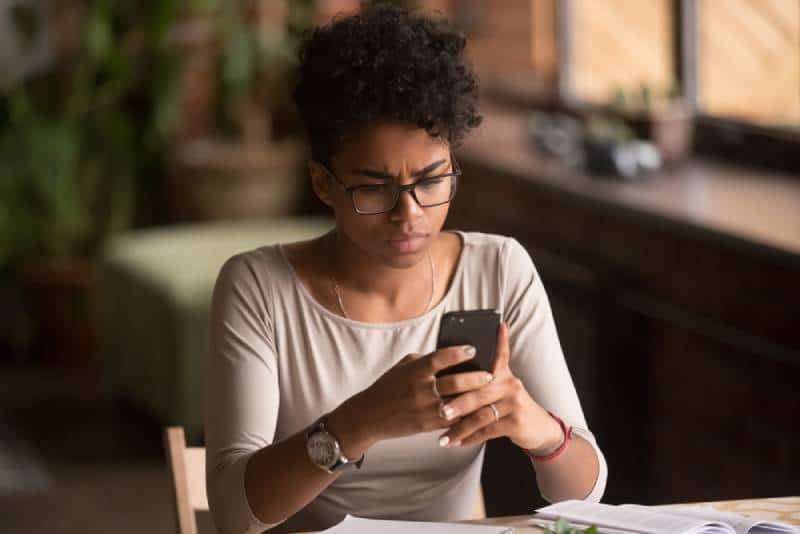 Angry confused african woman holding phone