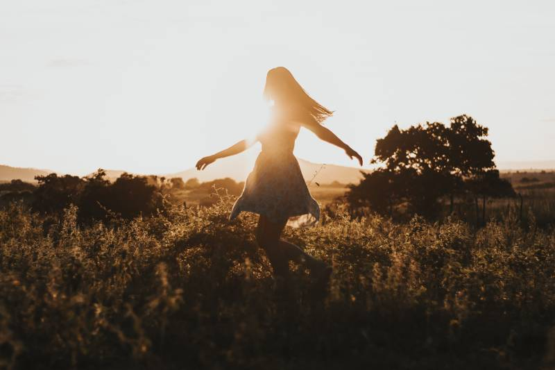 Silhouette of the woman dancing in the middle of the meadow