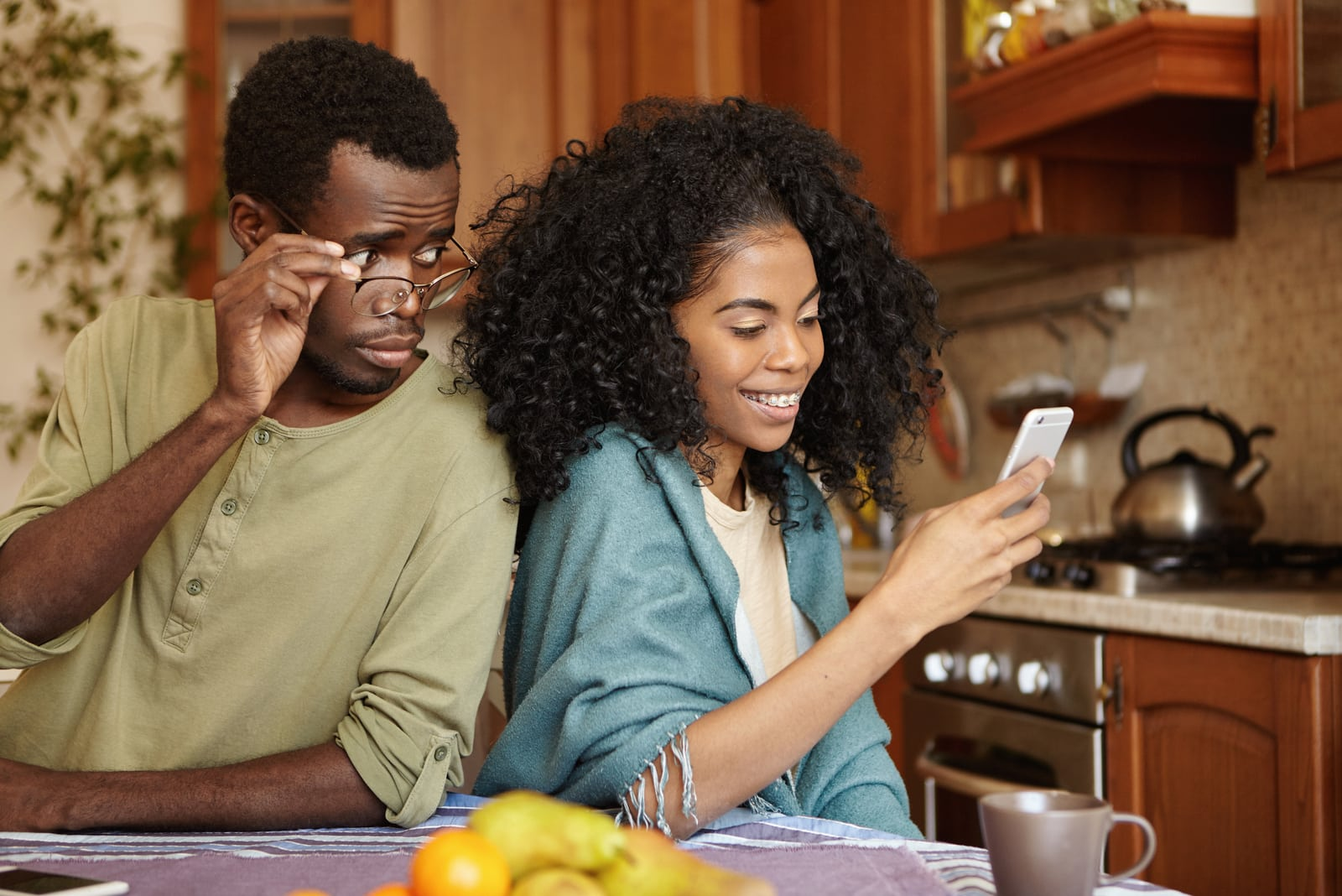 a jealous black man peeks into the contents of his wife's smartphone