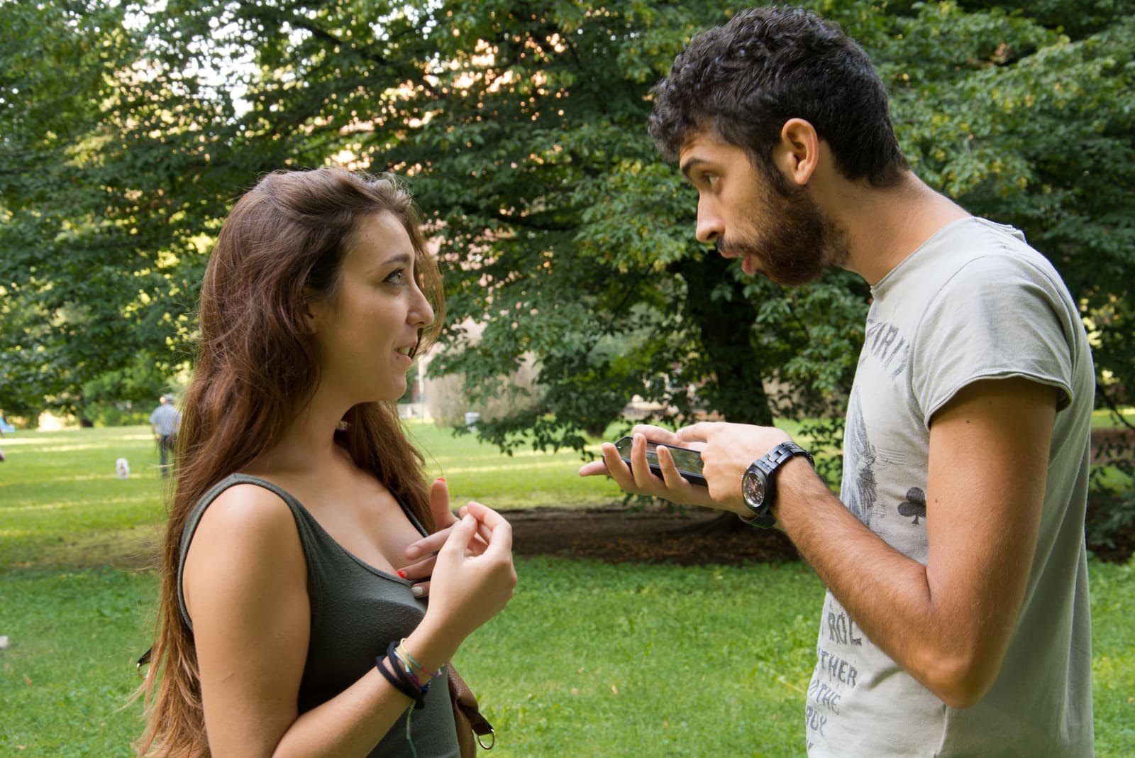a jealous man with a cell phone in his hand in a park is arguing with a girl