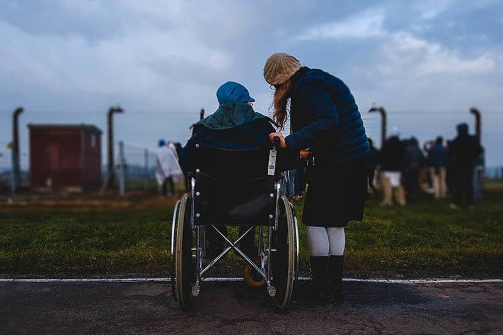 a woman standing with a man in a wheelchair