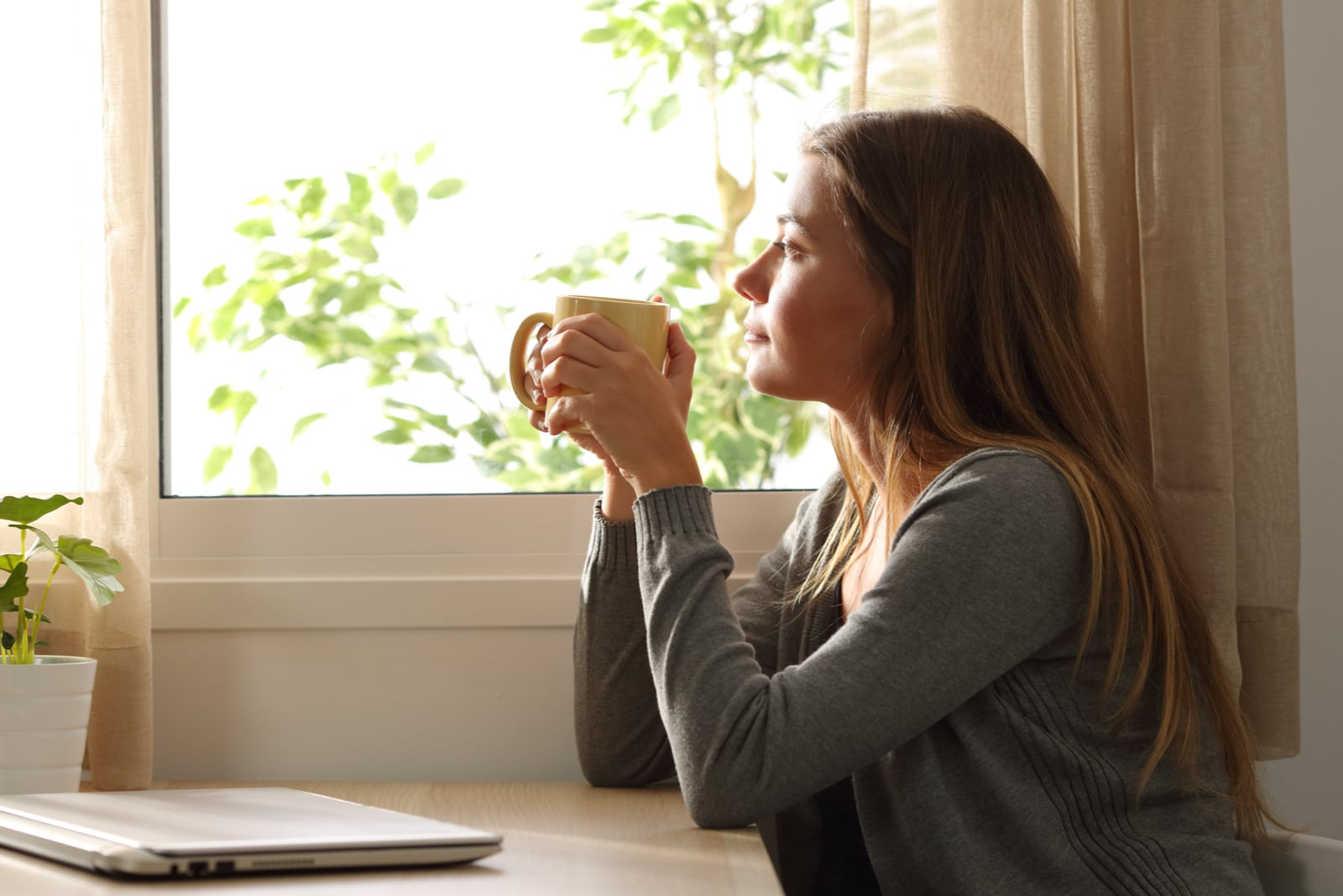 an imaginary woman sits and drinks coffee