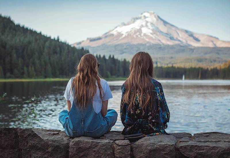 back view of two female friends sitting in front of water