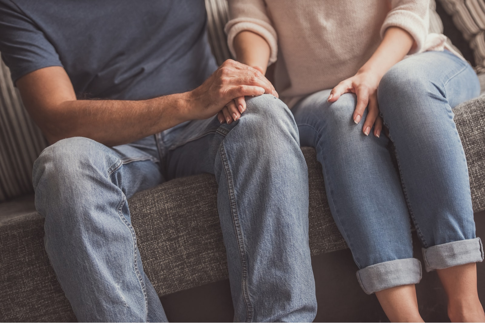 couple holding hands while resting on couch at home