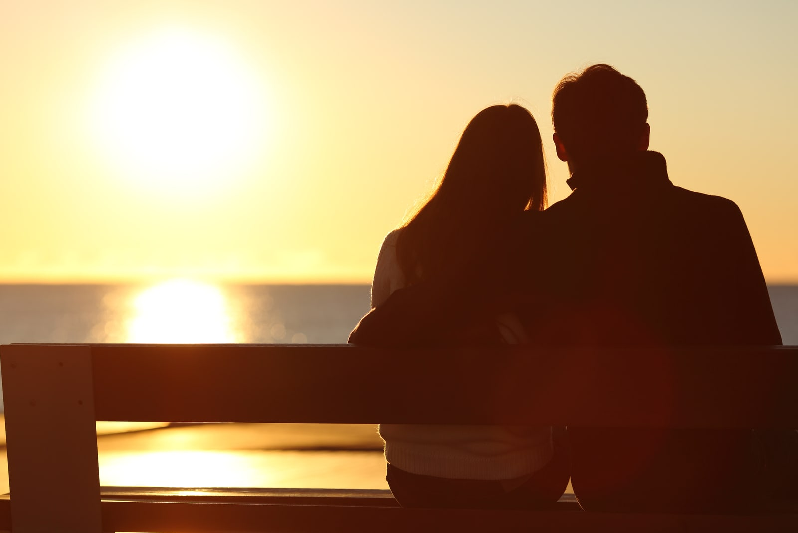 couple hugging and watching sun on the beach