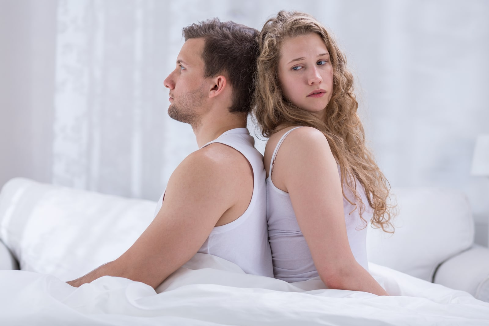 couple sitting on bed back to back