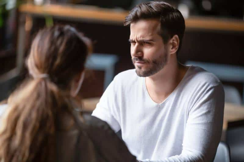 dissatisfied man looking at woman at cafe