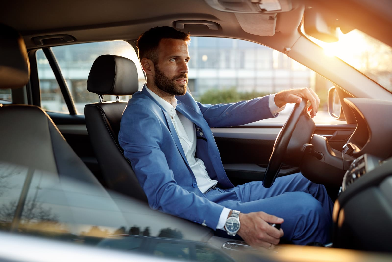 elegant man in business suit driving car