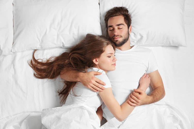 happy couple laying on bed