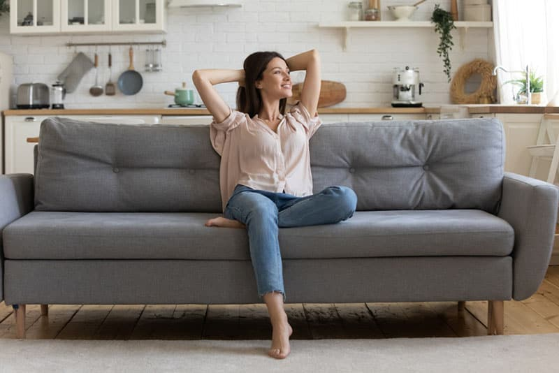 happy woman daydreaming on the couch