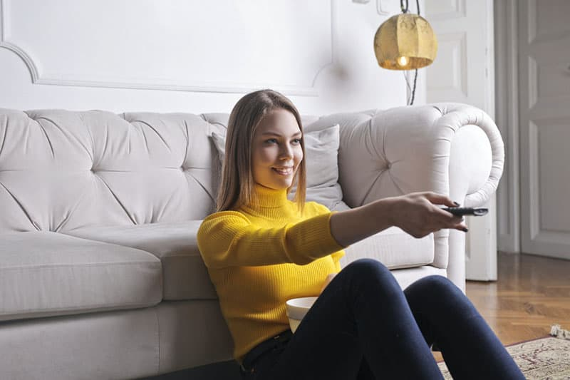 happy woman turning off tv
