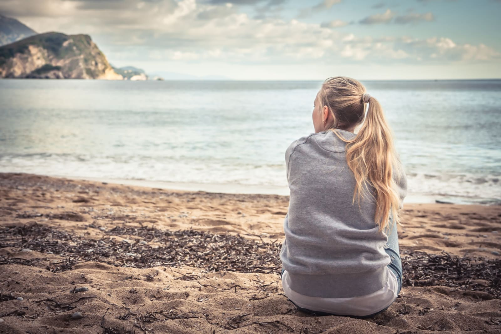 lonely young woman sitting on beach hugging her knees