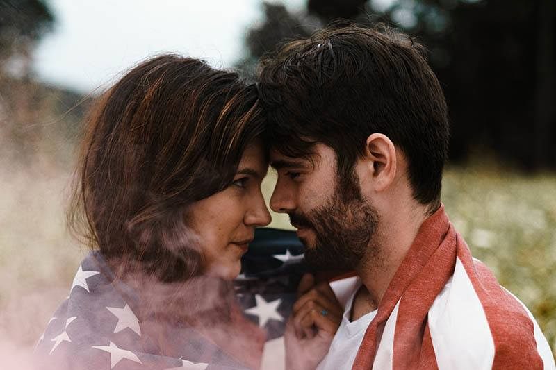 man and woman cuddling and looking each other in the eyes